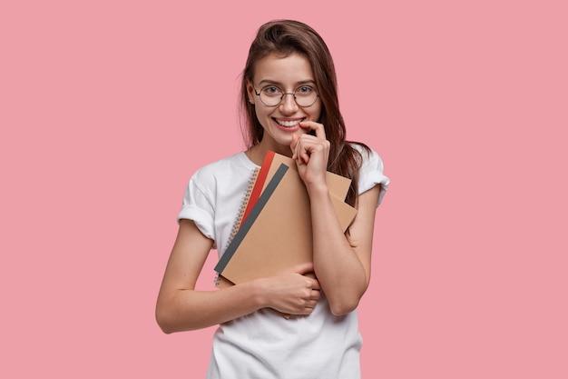 L'immagine della studentessa attraente tiene il dito vicino alla bocca, tiene il blocco note o l'organizzatore, vestita con una maglietta bianca casual, ha i capelli lunghi pettinati su un lato
