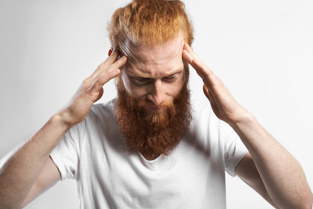 Picture of attractive stylish young unshaven european man in white t-shirt suffering from headache or migraine, squeezing temples to soothe pain. people, stress, sickness, depression and problems
