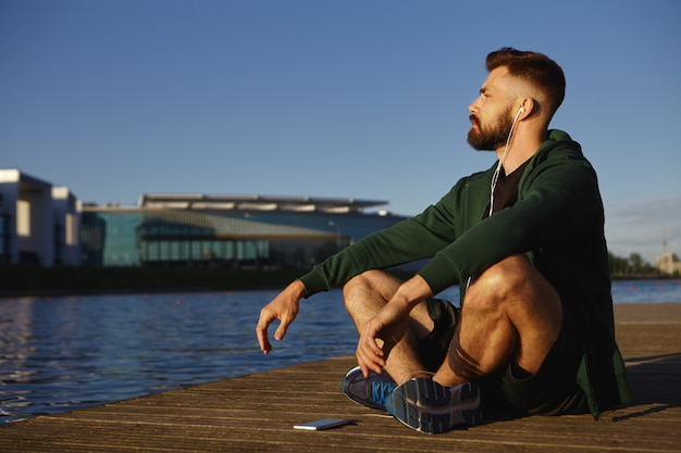 Picture of attractive unshaven young caucasian guy in running shoes sitting cross legged on wooden paving by lake meditating, listening to calm music using free application on his electronic gadget