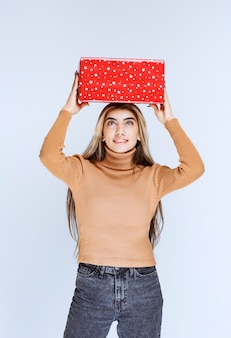 Picture of an attractive woman model holding a red present overhead.