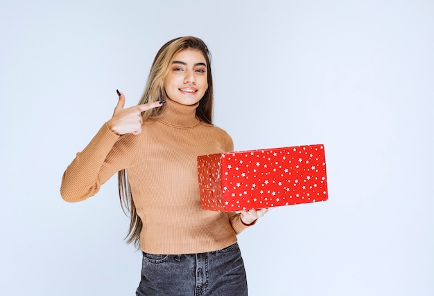 Picture of an attractive woman model holding a red present and pointing away .