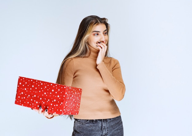 Picture of an attractive woman model holding a red present.