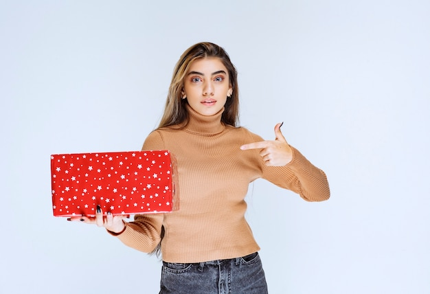 Picture of an attractive woman model pointing at a red present.