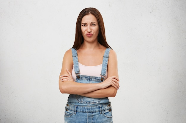 Picture of attractive young caucasian female with dark straight hair posing, keeping arms folded, having offended look, pouting lips, showing her dislike, negative attitude and rigidity