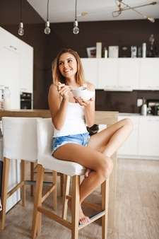 Picture of attractive young girl eating cornflakes with milk at kitchen