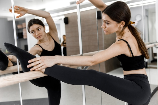 Picture of ballerina in studio. slim and slender girl standing in front of mirror and training.