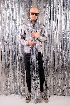 Picture of beautiful caucasian man without hair with black sunglasses in a shiny shirt, black leather pants and grey sneakers posing over silver glitter curtains