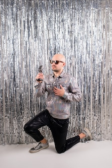 Picture of beautiful caucasian man without hair with black sunglasses in a shiny shirt, black leather pants and grey sneakers sings in a small silver microphone