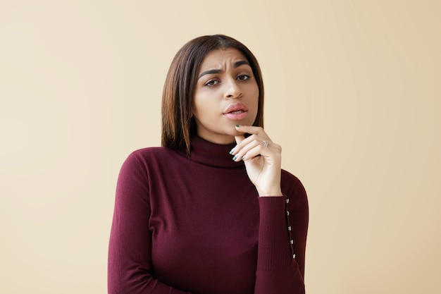 Picture of beautiful doubtful young afro american woman raising one eyebrow and touching chin, feeling indecisive or suspicious, looking with eyes full of doubts, disrtust and suspicion