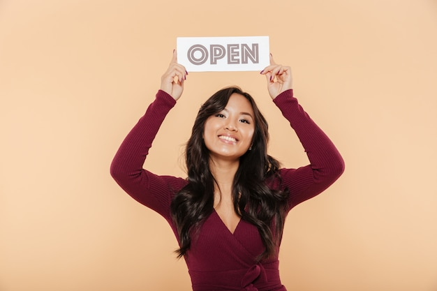 Picture of beautiful woman in maroon dress holding sign with word open over head being friendly on peach background