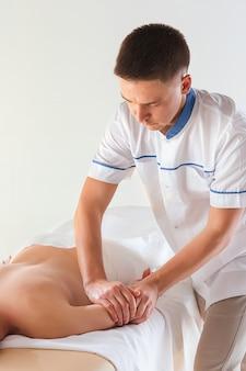 L'immagine di bella donna nel salone di massaggio e le mani maschii sul suo corpo