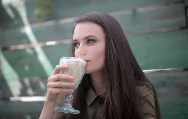 Picture of a beautiful woman with mesmerizing  green eyes drinking a coffee