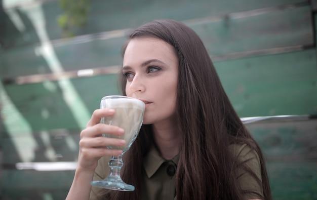 Immagine di una bella donna con affascinanti occhi verdi che beve un caffè