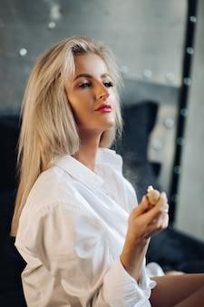 L'immagine di una bellissima giovane donna caucasica con lunghi capelli biondi in camicia da uomo posa per la telecamera in cucina