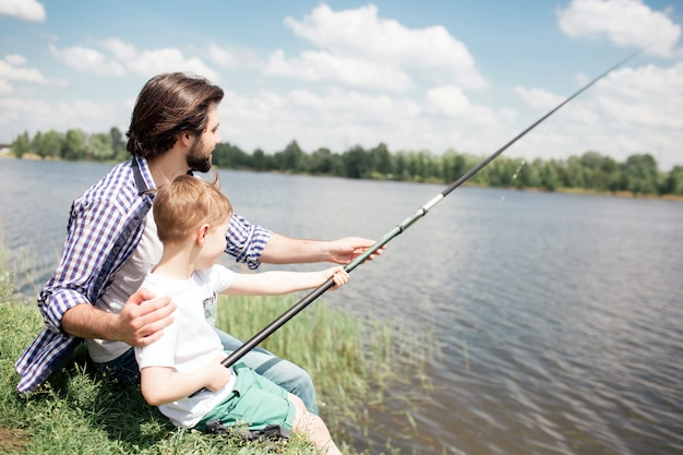 A picture of boys sitting together at the edge of lake and fishing. boy is holding long fish-rod while his dad is guiding him to fishing right.