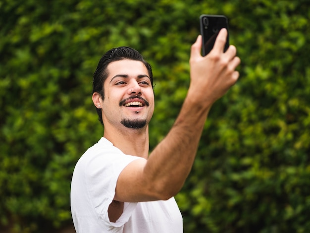 Picture of a brunette male taking selfies against a greenery
