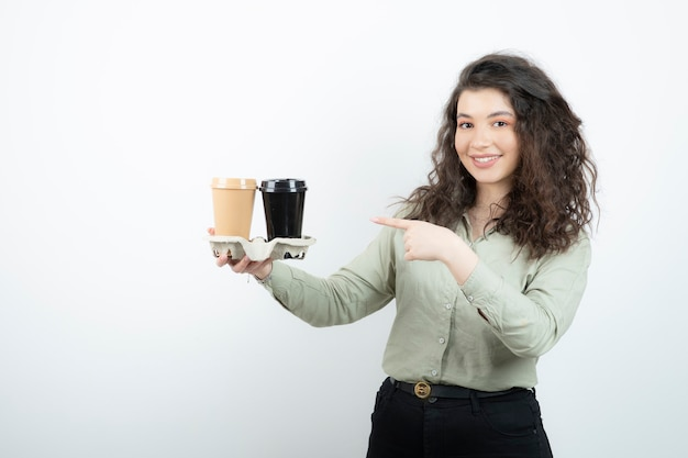 Picture of a brunette woman standing and pointing at two cups in a carton .