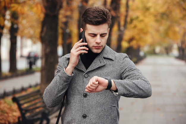 Picture of businesslike man speaking on mobile phone while going on meeting, checking time with watch on hand