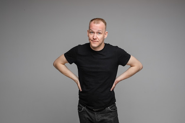 Picture of caucasian male wearing a t-shirt and jeans isolated over the grey wall