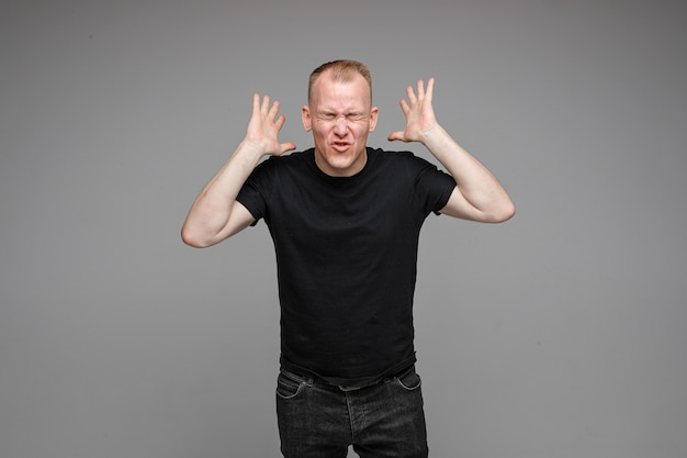 Picture of caucasian man keeps his hands near the head rages isolated on grey wall