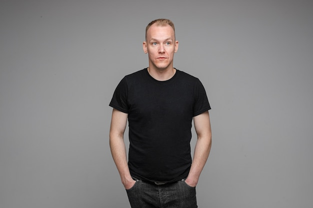 Picture of caucasian man keeps his hands in the pockets of his black jeans isolated on grey wall