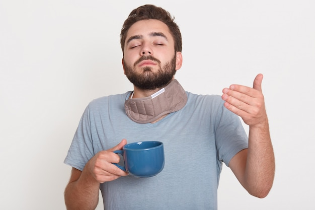 Picture of charismatic good looking young man closing eyes, holding cup with hot drink, enjoying smell of coffee, wearing pajamas