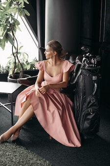 Picture of a charming caucasian lady sits on the black leather armchair and poses for the camera