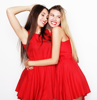 Picture of a charming young girls in red dress on white