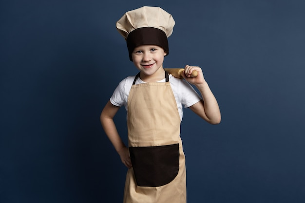 Picture of cheerful blue eyed 7 year old boy cook in chef uniform holding rolling pin on his shoulder, being glad while kneading dough for gingerbread cookies, looking at camera with happy smile