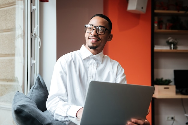Picture of cheerful businessman wearing glasses sitting near window and typing by laptop computer