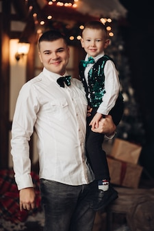 Picture of cheerful caucasian dad has a lot of fun with his little cute son in the new year atmosphere at home