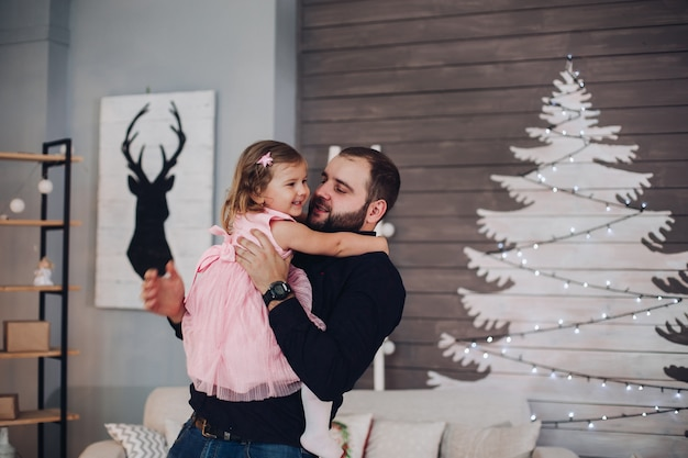 Picture of cheerful caucasian dad rejoices and has a lot of fun with his little cute daughter in pink dress in the new year atmosphere at home