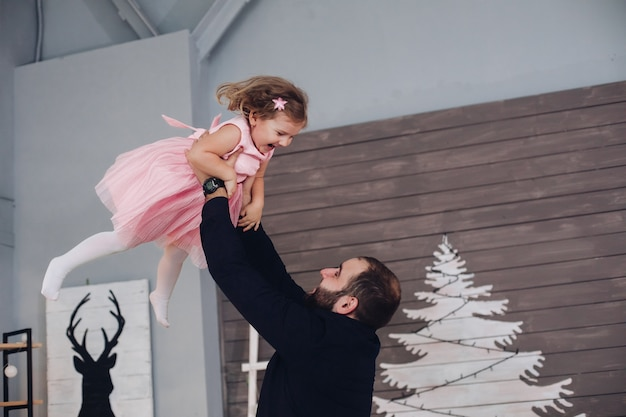 Picture of cheerful caucasian dad with short dak hair rejoices and has a lot of fun with his little cute daughter in pink dress in the new year atmosphere at home