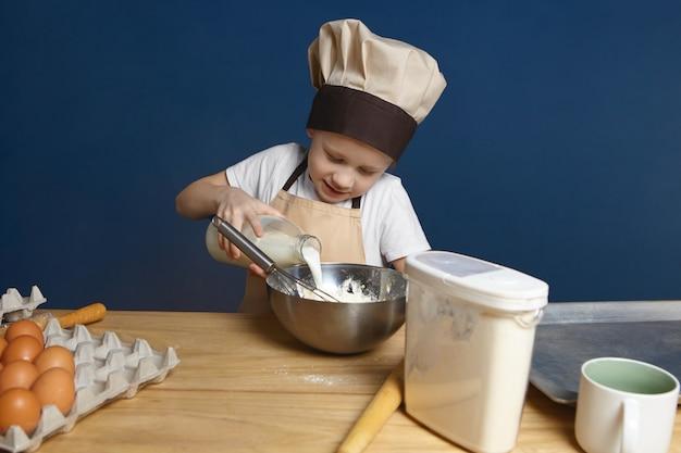 Immagine del ragazzino allegro in grembiule e cappuccio che cucina dessert al grande bancone in legno con le uova