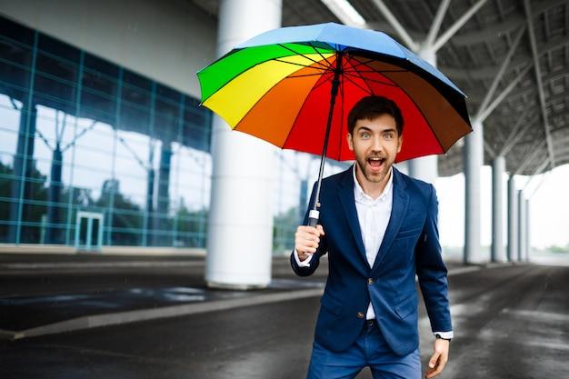 Immagine di giovane uomo d'affari allegro che tiene ombrello eterogeneo nella via