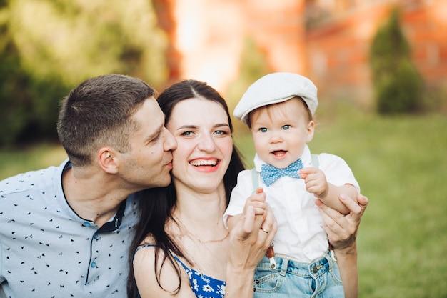 L'immagine di una giovane femmina e di un maschio caucasici allegri tiene il bambino per mano, sorride e si rallegra