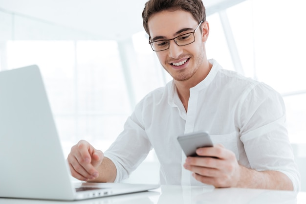 Picture of cheerful young man dressed in white shirt using laptop computer. look at phone.
