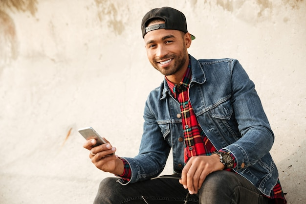 Picture of cheerful young man wearing cap walking on the beach and chatting by his phone.