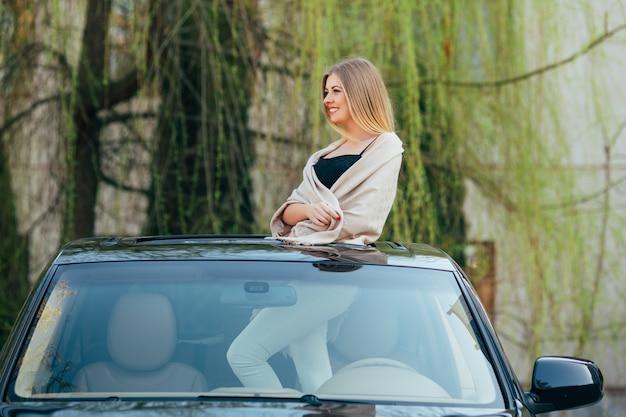 Immagine della giovane donna allegra che indossa occhiali da sole e mani alzate sul tetto apribile dell'auto di lusso