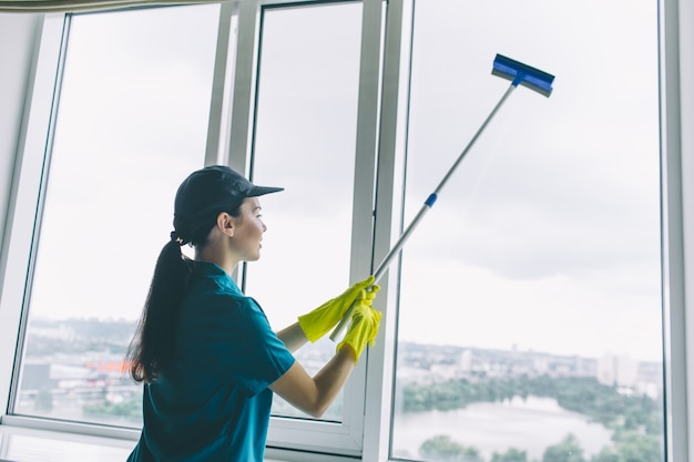 A picture of cleaner works at window. she cleans it with mop. girl is concentrated. she does it careful.