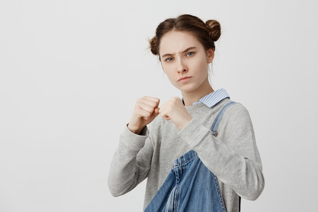 Picture of concentrated woman wearing casual standing in defensive position with clutching fists. feminine girl with strict gaze ready to fight being offended with street thief. body language