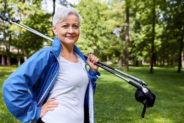 Picture of confident beautiful caucasian female pensioner in her sixties enjoying retirement, holding trekking poles on her shoulder, going to have nordic walking outdoors, keeping hand on waist