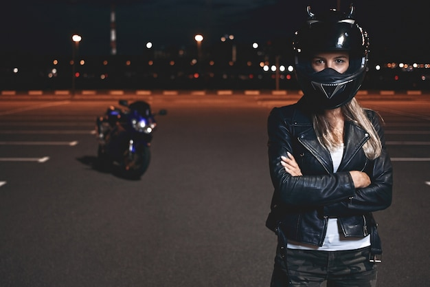 Picture of confident self determined young female rider in safety helmet standing in parking lot keeping arms crossed and looking, going to have ride on motorcycle around night city