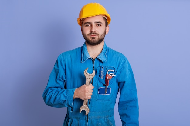 Picture of confident strong young builder holding wrench in one hand, , wearing blue uniform, standing isolated over blue wall in studio. people and work concept.