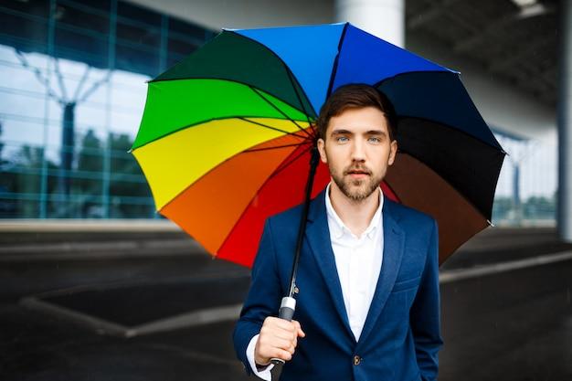 Immagine di giovane uomo d'affari sicuro che tiene ombrello eterogeneo nella via