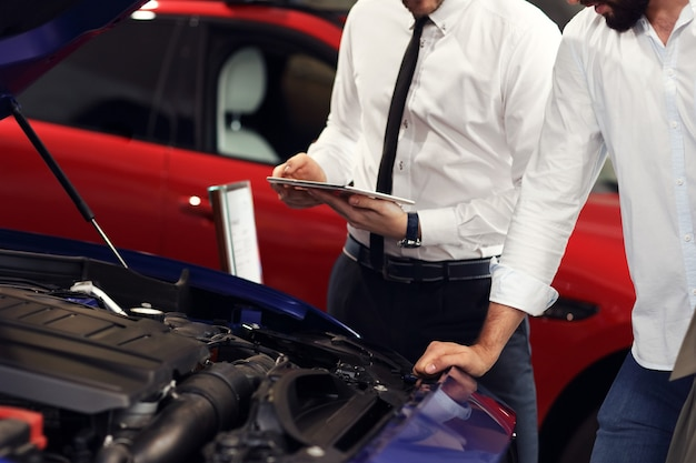 Picture of confident young salesman explaining all the car features to the young attractive owners
