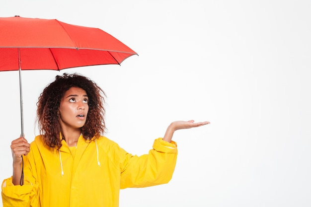 Picture of confused african woman in raincoat hiding under umbrella and waiting raing over white