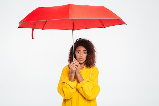 Picture of confused african woman in raincoat hiding under umbrella over white