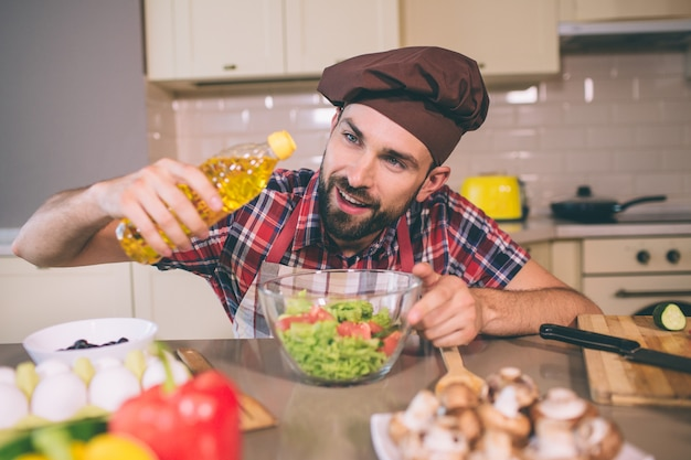 A picture of cook standing at table and holds bottle of sunflower oil. he looks at it and pouring some oil into bowl with salad. man is doing that careful. also he holds another hand on bowl.