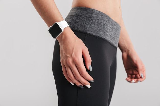 Picture cropped of female sport instructor standing with watch on wrist, isolated over gray wall